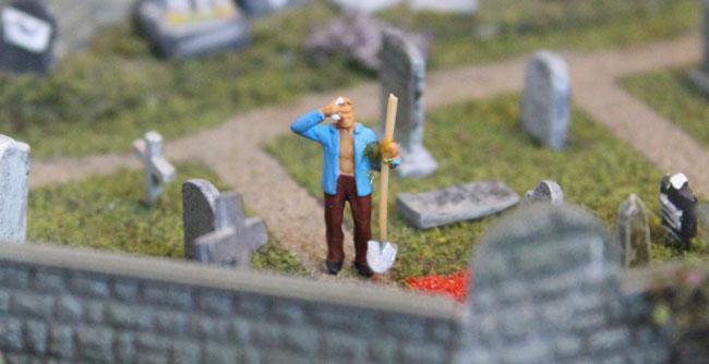 modelspoor man met schep op begraafplaats