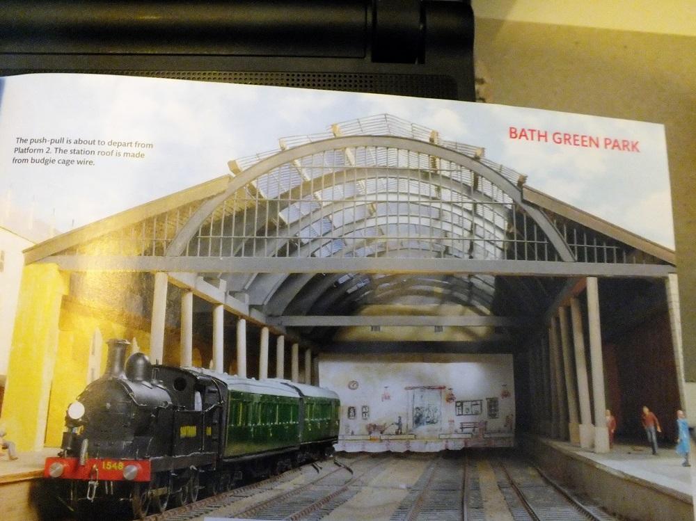 Brits modelbaan Bath Green de stationsoverkapping. De achterwand is geschilderd en suggereert een loopperron (het zijn kopsporen). Lok omlopen gebeurt via de sporen in de bogen in de linkerhoek van de tafel